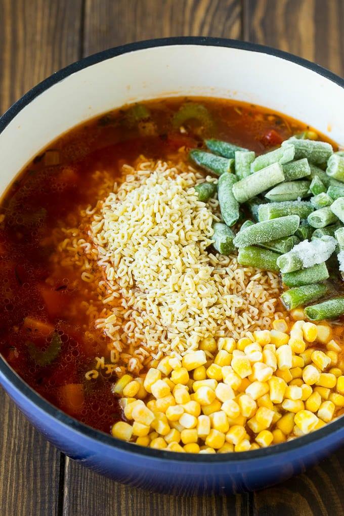 A pot of soup with alphabet noodles, frozen corn and frozen green beans.