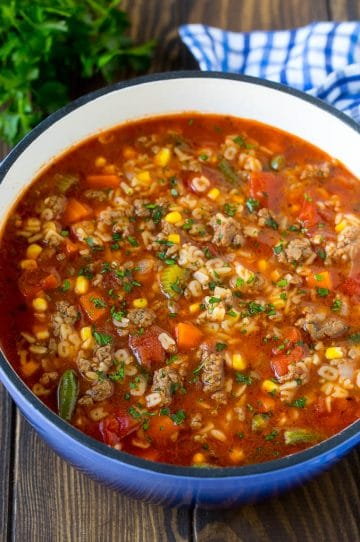 A pot of alphabet soup with ground beef and vegetables.
