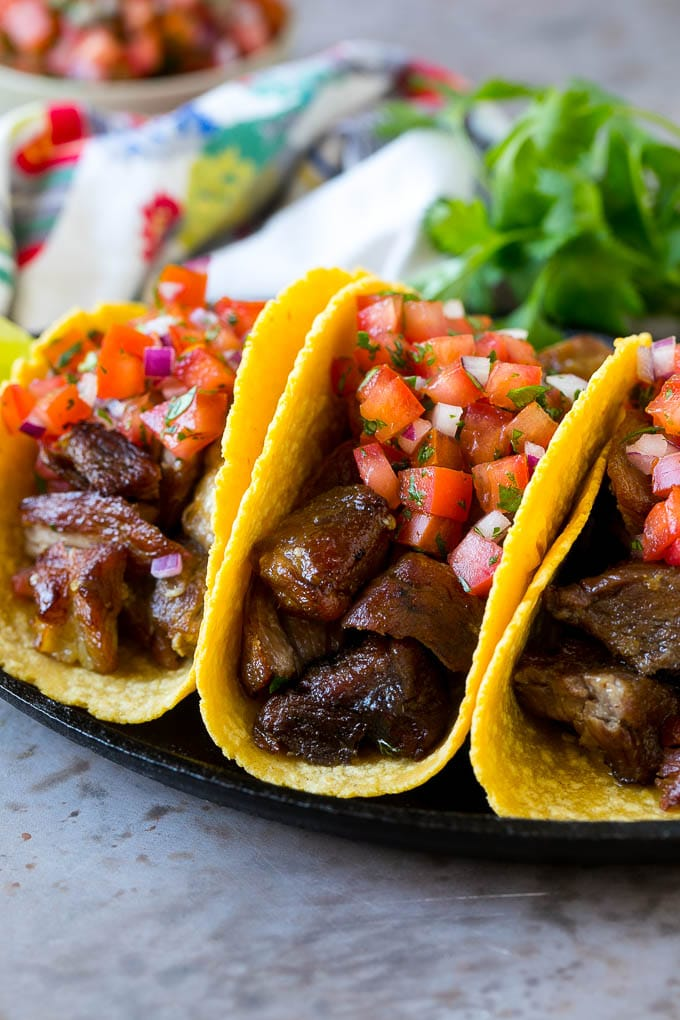 Pork carnitas tacos in corn tortillas, topped with pico de gallo.