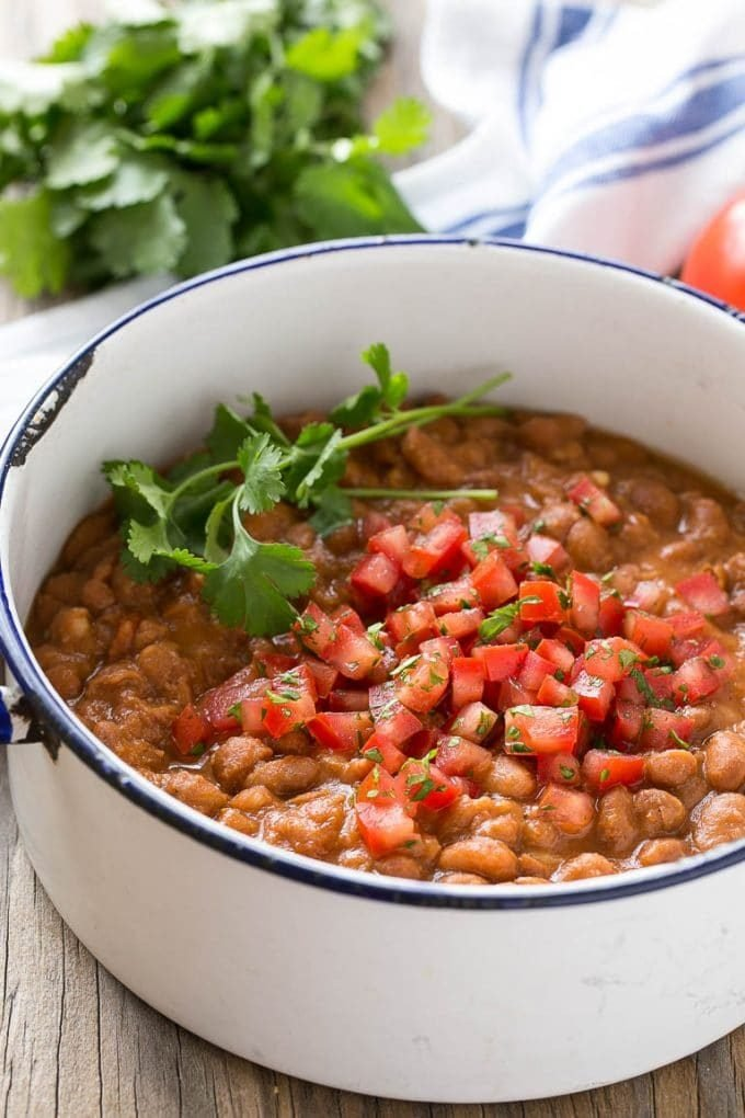 A pot of pinto beans topped with diced tomatoes and cilantro.