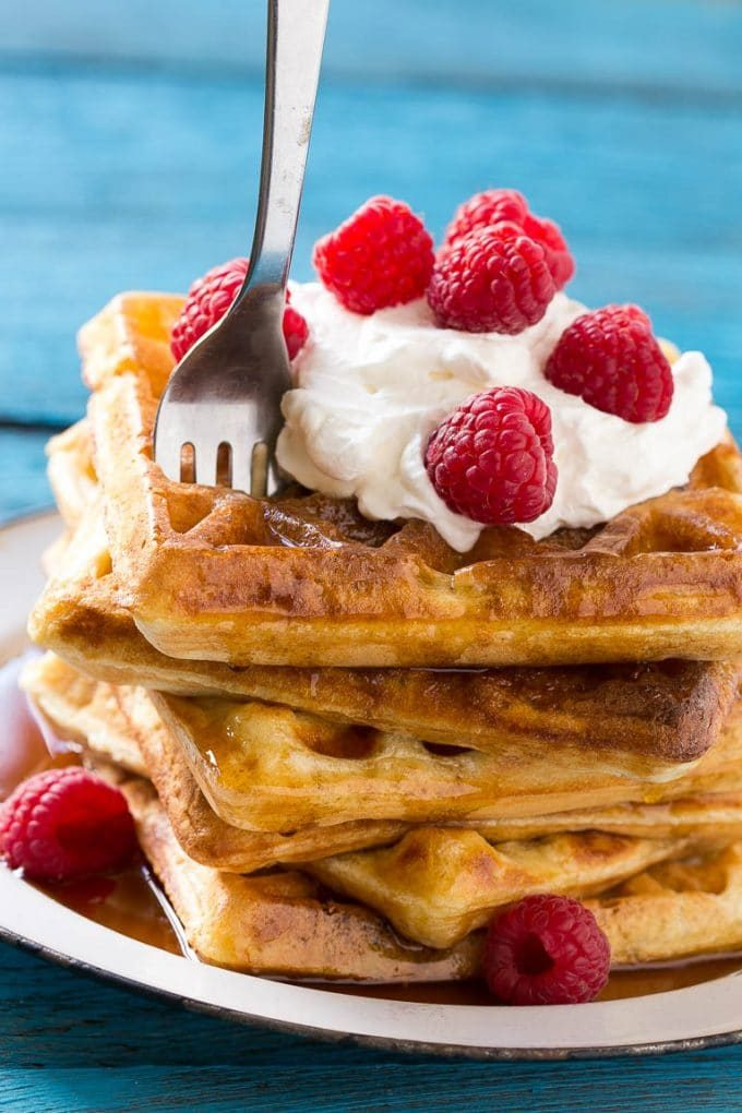 A fork in a stack of yeast raised waffles.