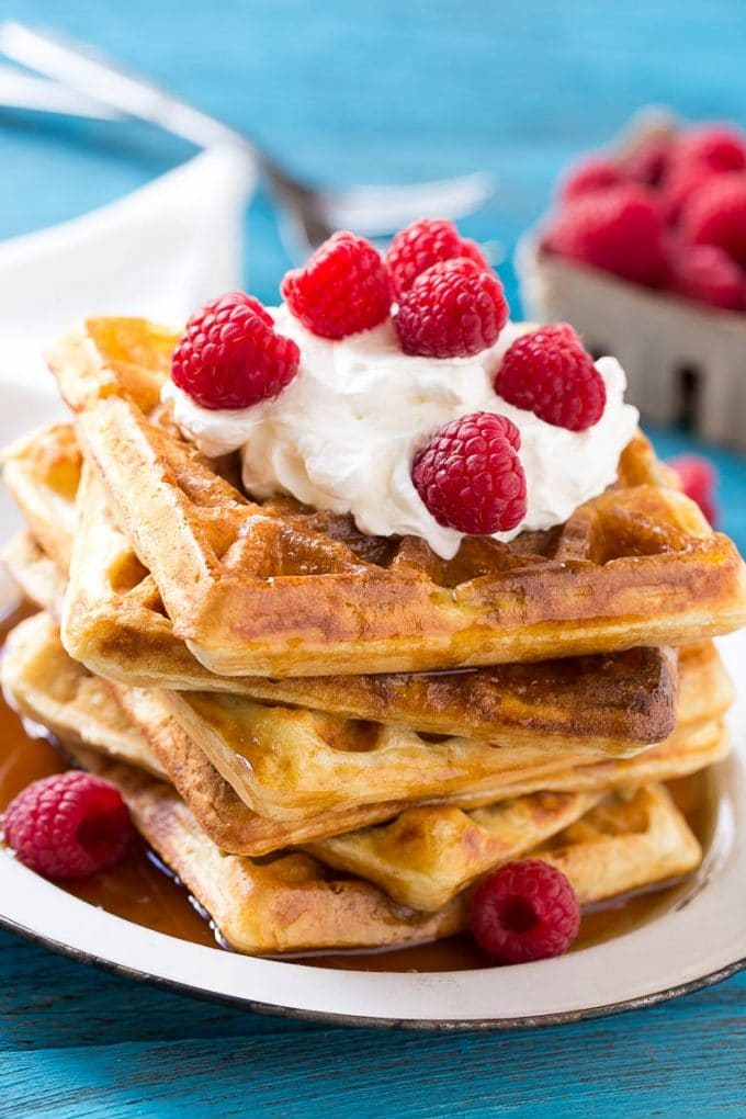 Overnight waffles garnished with whipped cream and raspberries.