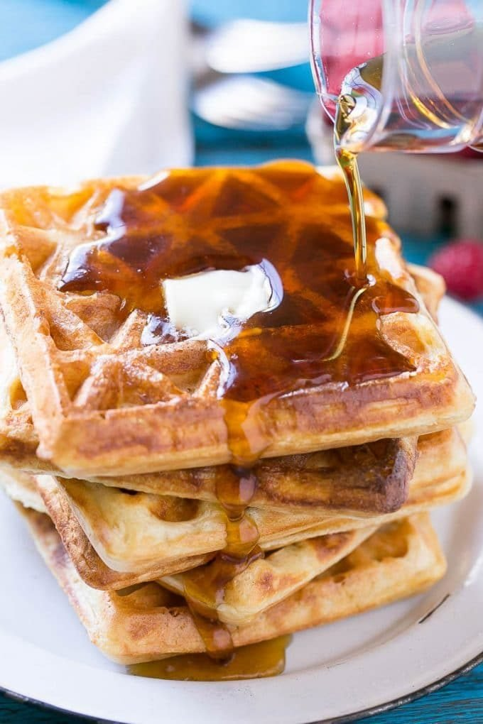 A stack of yeast waffles topped with butter and maple syrup.