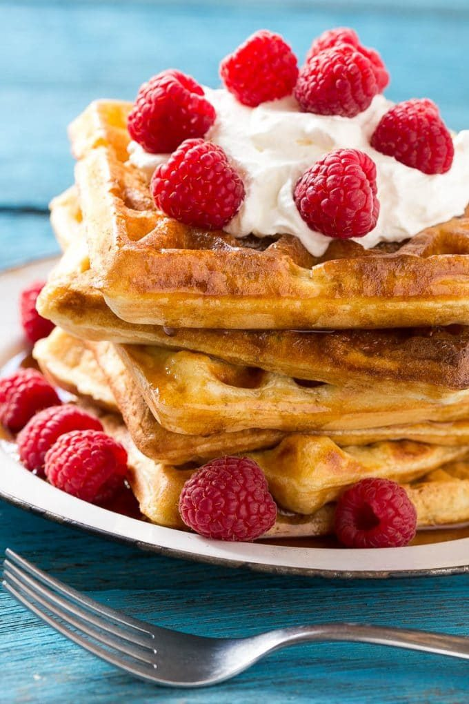 Yeast waffles topped with maple syrup, whipped cream and berries.