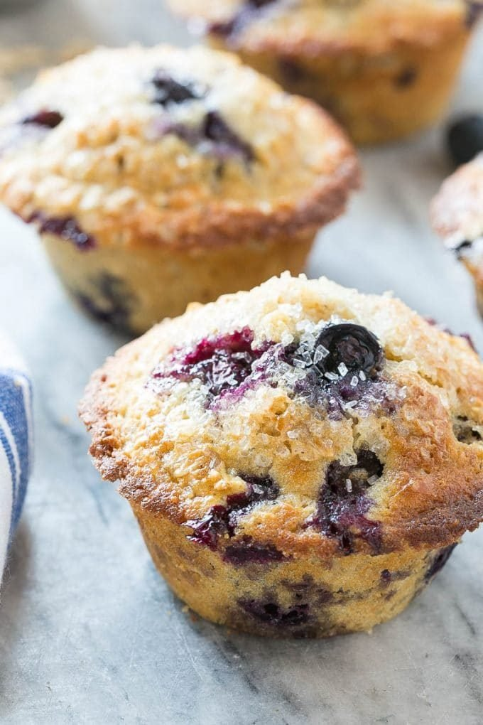 An oatmeal blueberry muffin topped with coarse sugar.