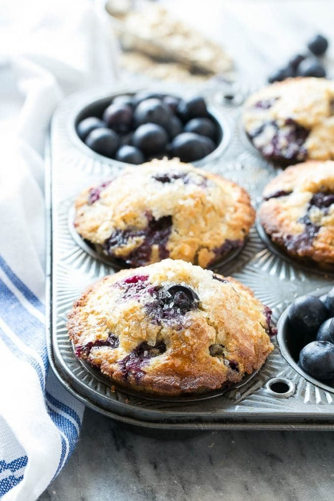 Healthy blueberry muffins in a muffin tin surrounded by fresh berries.