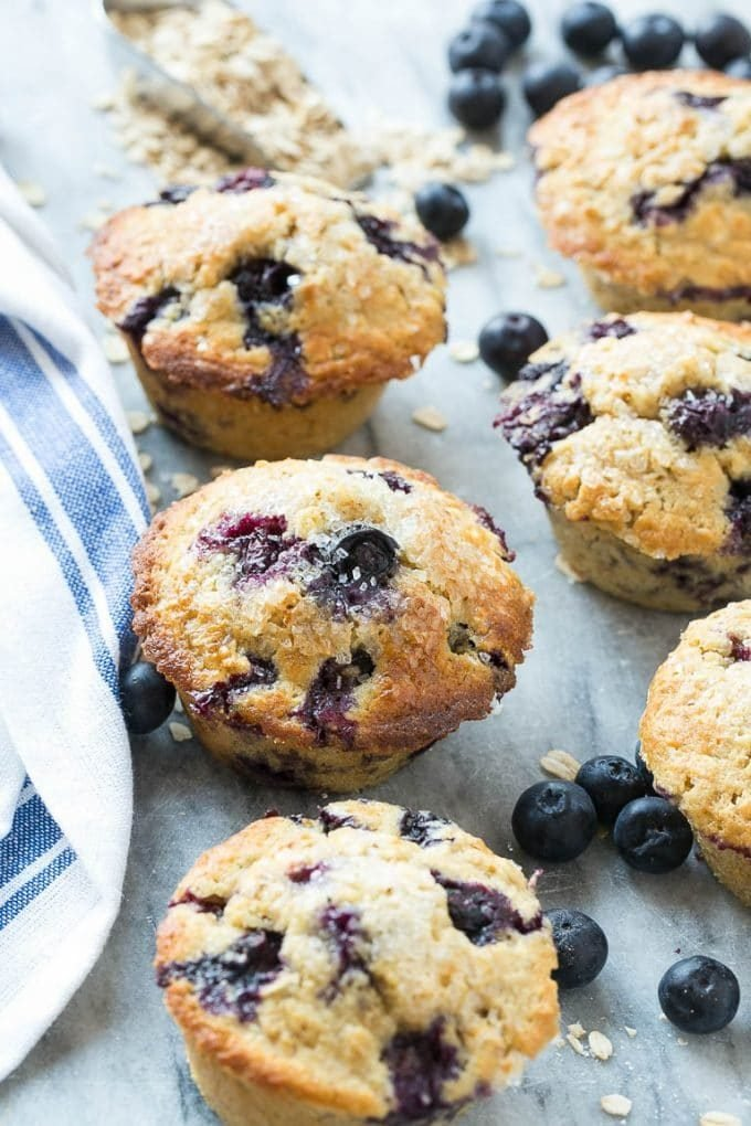 An assortment of healthy blueberry muffins surrounded by berries and oats.
