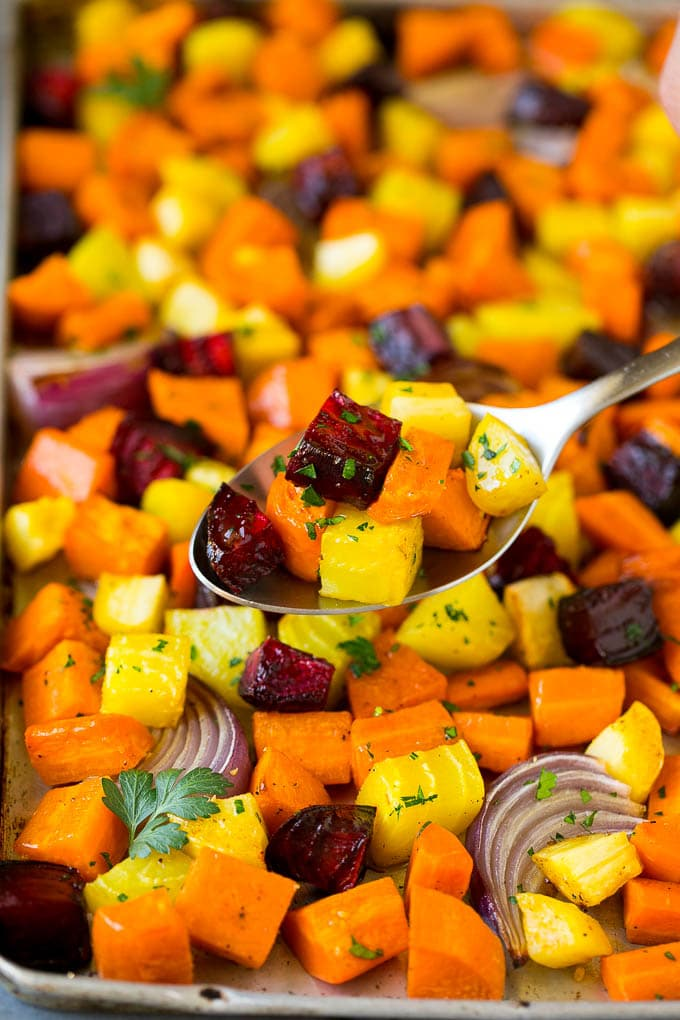 A spoon serving up a portion of roasted vegetables.