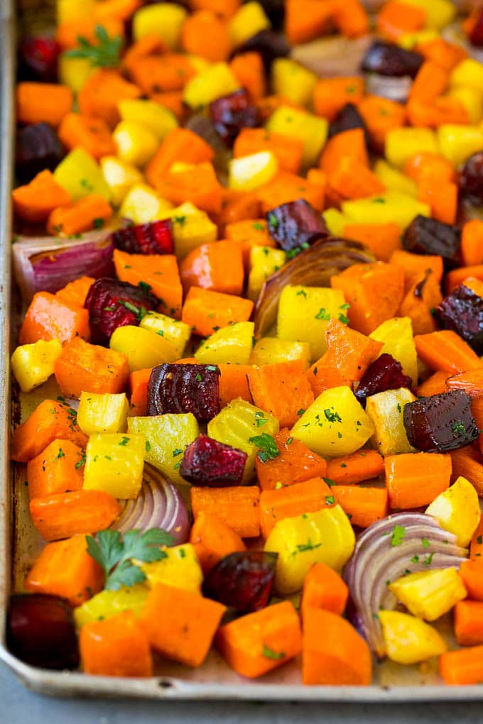Roasted root vegetables on a sheet pan, topped with chopped parsley.