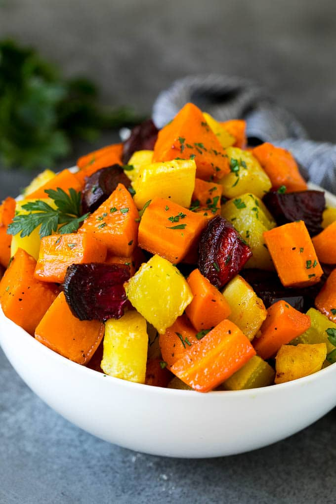 A bowl of diced roasted root vegetables topped with parsley.