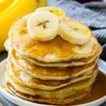 A stack of banana pancakes with banana slices and maple syrup.
