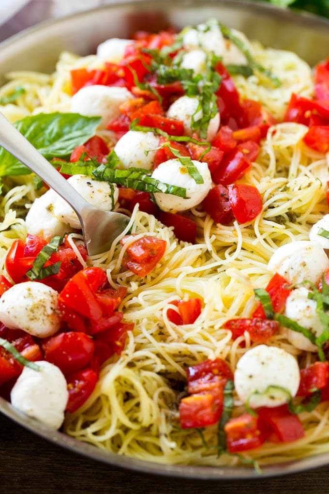 A pan of caprese pasta with angel hair pasta, olive oil, fresh basil, tomatoes and mozzarella cheese.