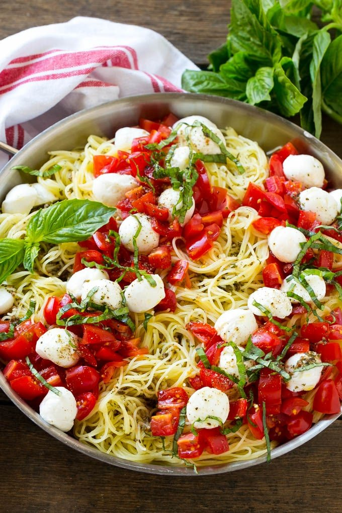 A pan of angel hair caprese pasta topped with olive oil, tomatoes, basil and fresh mozzarella.