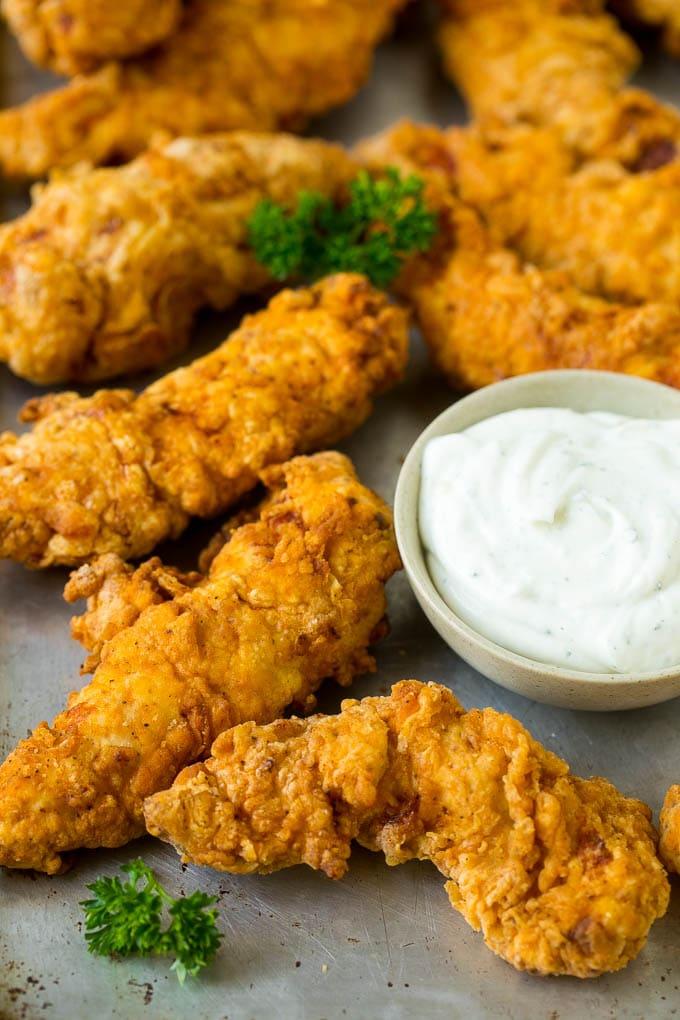 Crispy chicken tenders on a sheet pan.