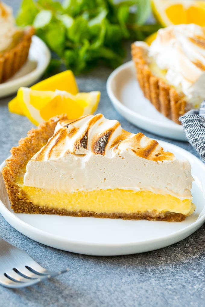 A slice of lemon meringue tart with creamy lemon filling and brown sugar meringue topping.