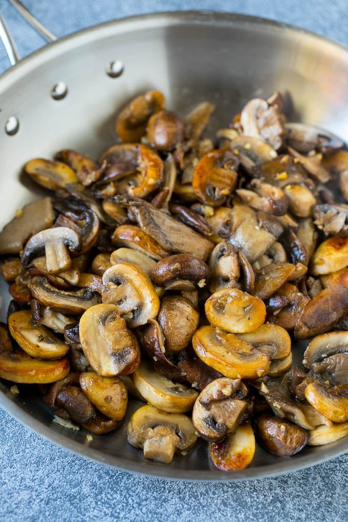 An assortment of sauteed mushrooms in a skillet.