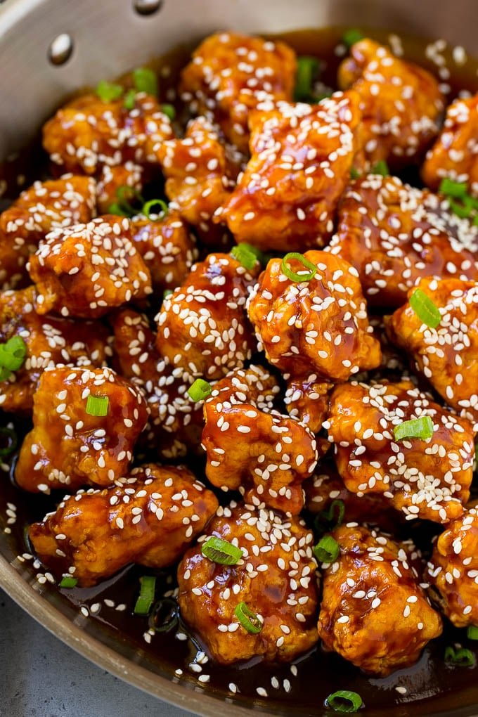 Crispy sesame chicken in a pan, coated in a sweet and savory sauce and sesame seeds.