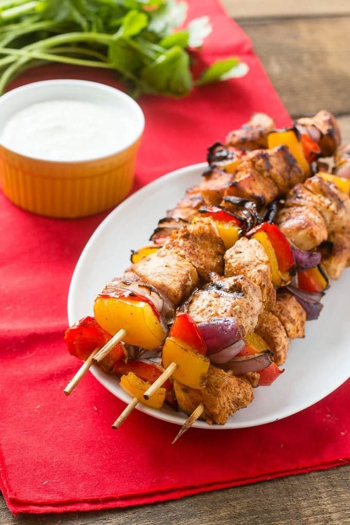 A plate of chicken fajita kabobs served with cilantro sauce.