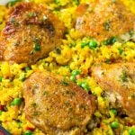A pan of arroz con pollo with chicken thighs, saffron rice and peas.