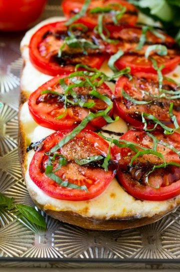A split loaf of bread on a sheet pan topped with fresh mozzarella cheese, sliced red tomatoes, thinly sliced basil and balsamic glaze.