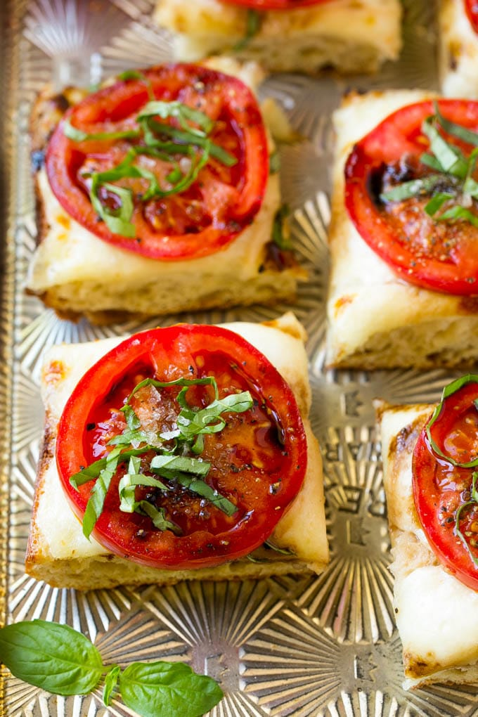 Bread cut into squares topped with melted mozzarella cheese, tomato slices, basil and balsamic glaze.