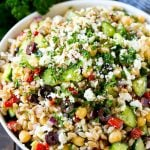 Farro salad made with cuucmber, feta cheese, olives and peppers, topped with parsley.