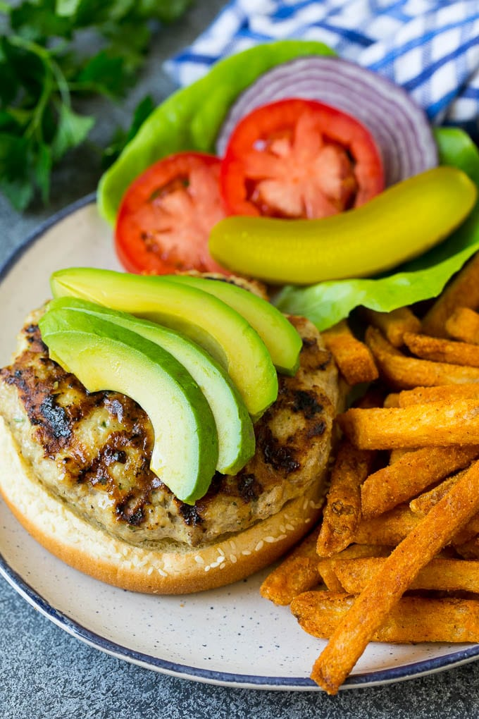 An open faced turkey burger topped with sliced avocado.