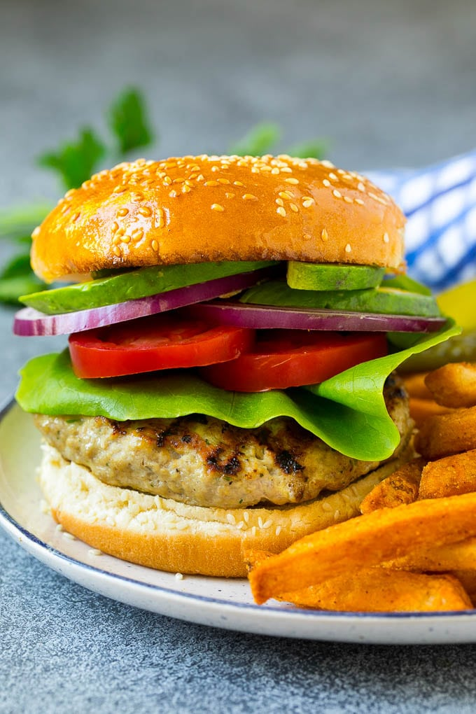 A turkey burger topped with lettuce, tomato, pickles and onion.