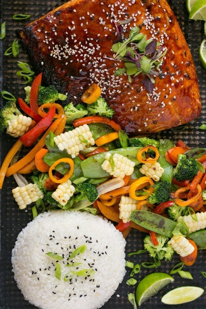 A sheet pan with hoisin glazed salmon, mixed vegetables and steamed rice.
