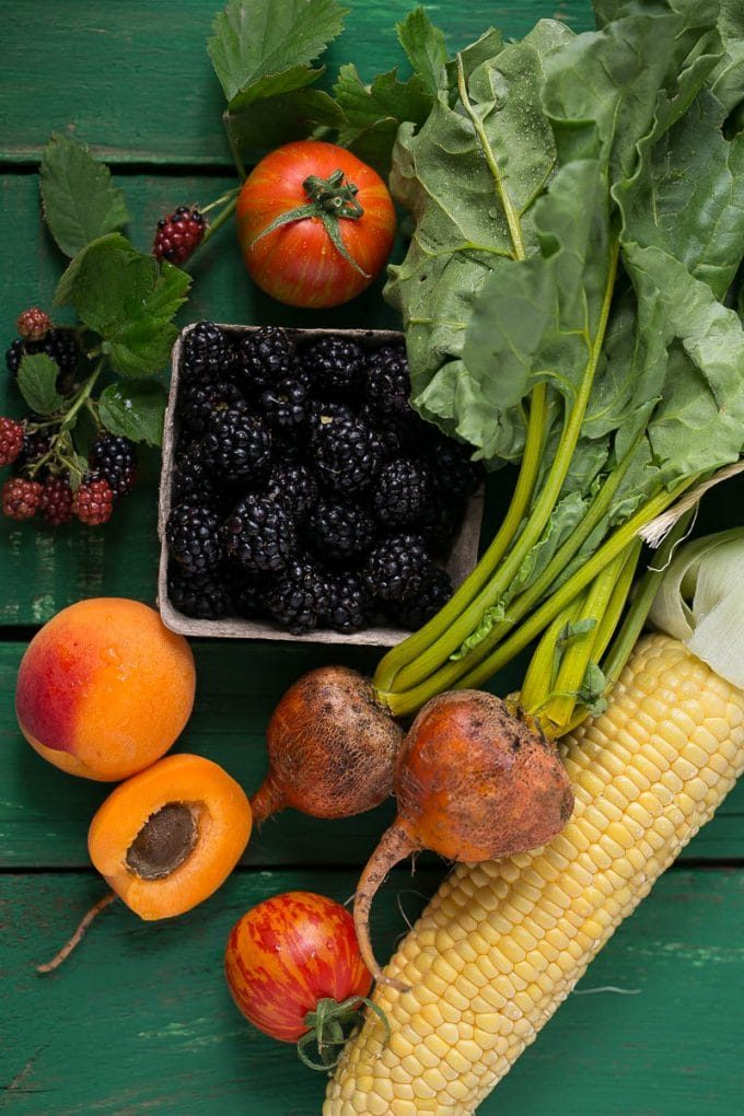 A selection of produce including corn, beets, apricots, tomatoes and blackberries.