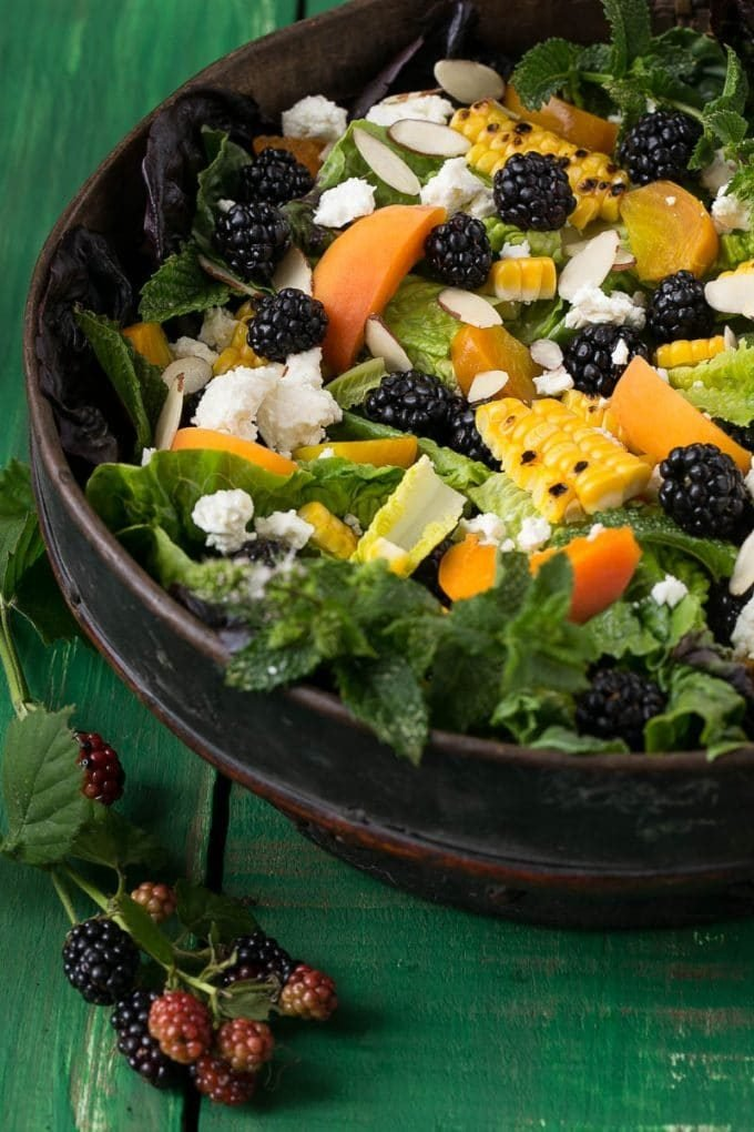 A salad bowl filled with lettuce, fresh produce, cheese and almonds.