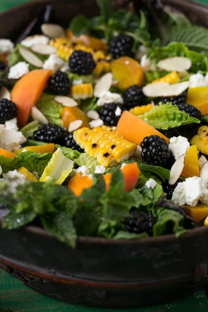 A bowl of lettuce topped with berries, corn, feta cheese and apricots.