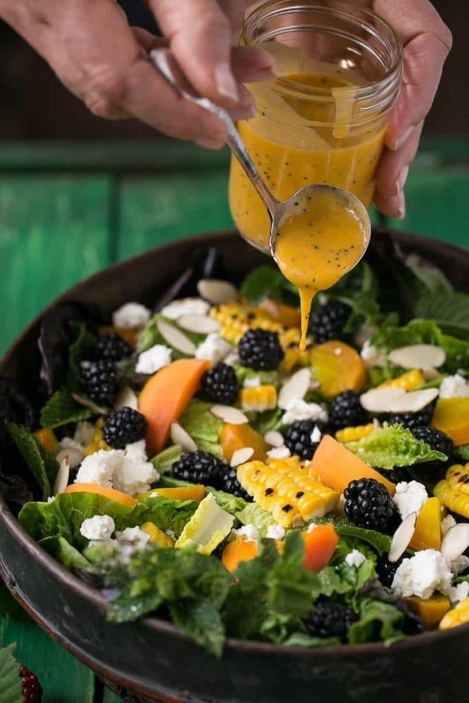 A hand spooning apricot dressing on top of a salad.