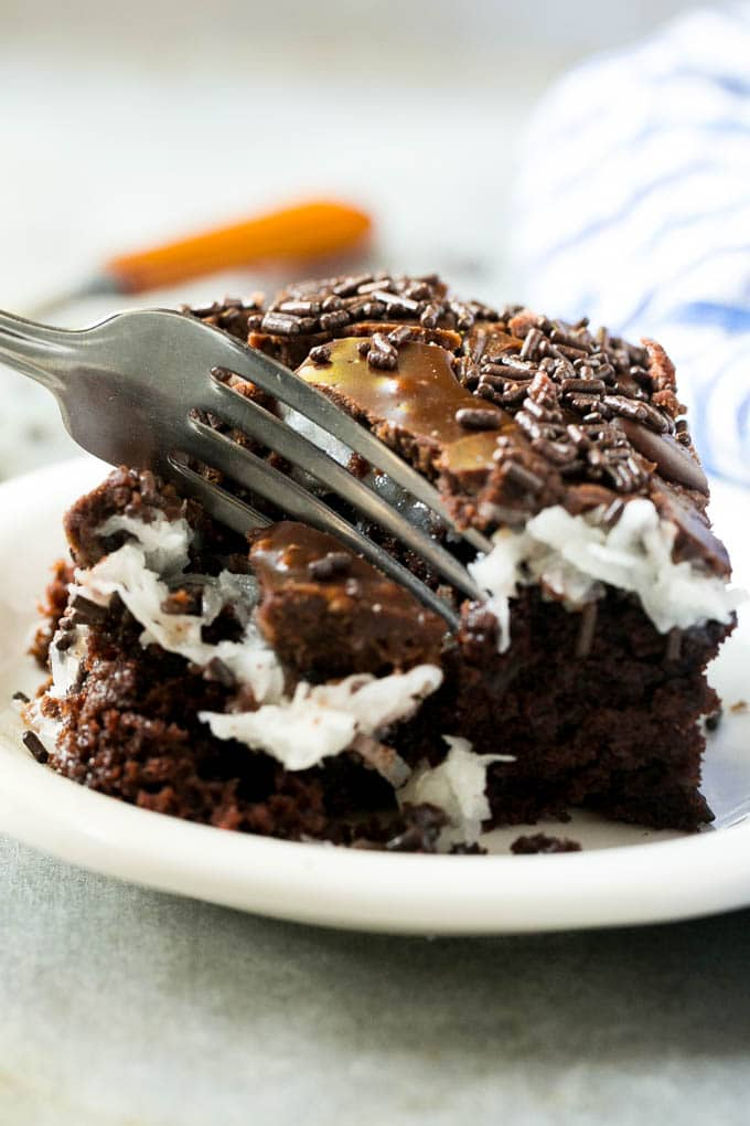 A fork taking a piece of chocolate coconut cake.