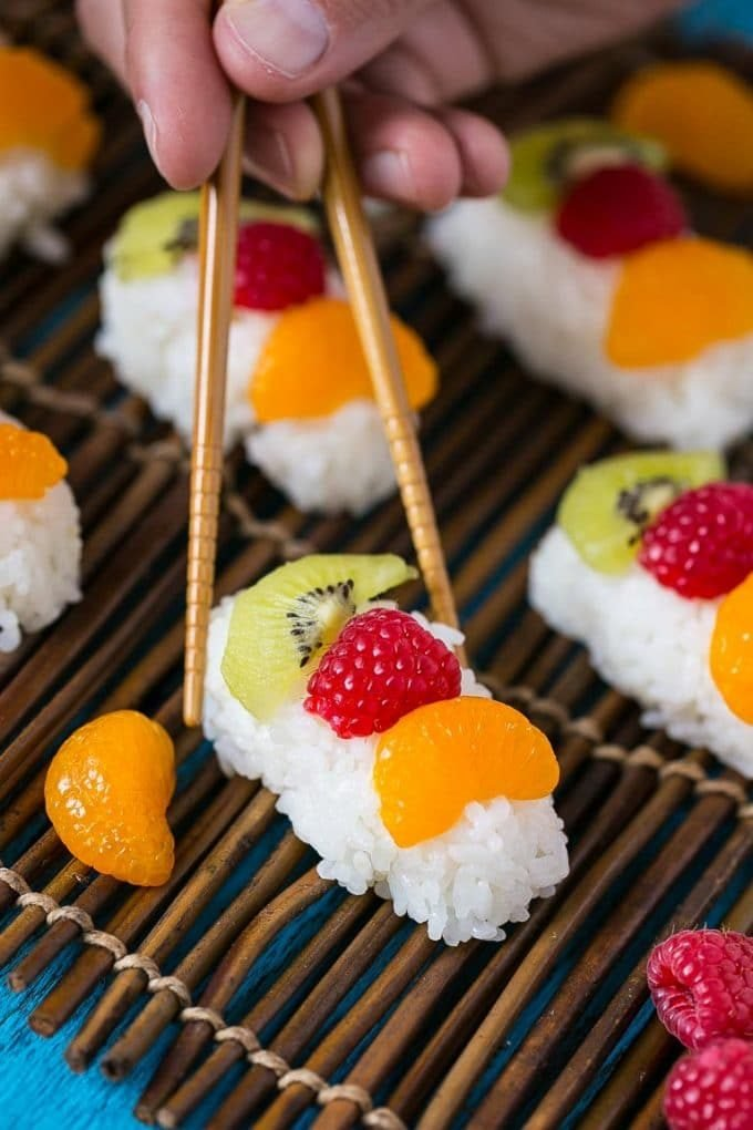 Chopsticks going to pick up a piece of dessert sushi.