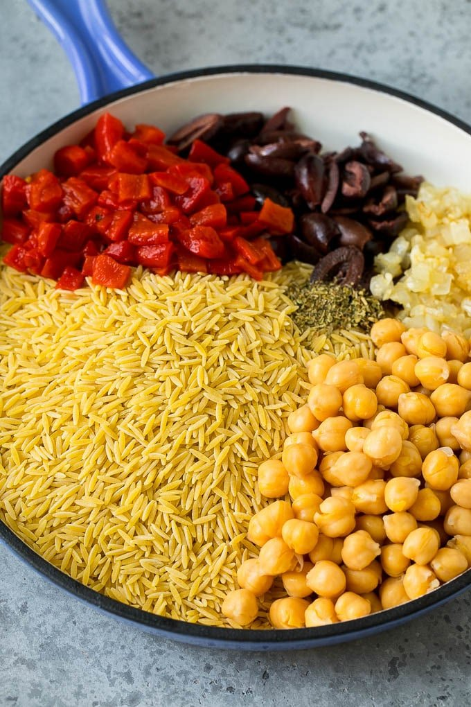 Orzo pasta, olives, chickpeas and roasted peppers in a skillet.