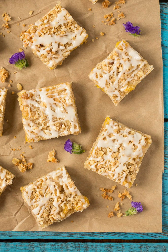 These peach almond crumble bars feature ripe juicy peaches in a brown sugar oatmeal crust, all topped off with almond streusel and vanilla glaze.