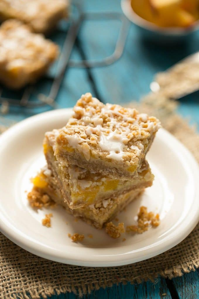 These peach almond crumble bars feature ripe juice peaches in a brown sugar oatmeal crust, all topped off with almond streusel and vanilla glaze.
