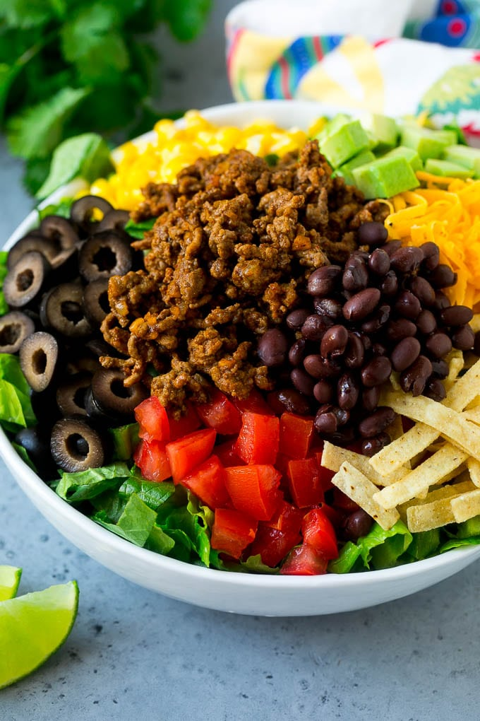 Ground beef, tortilla strips, beans, tomatoes, olives, corn and avocado over lettuce.