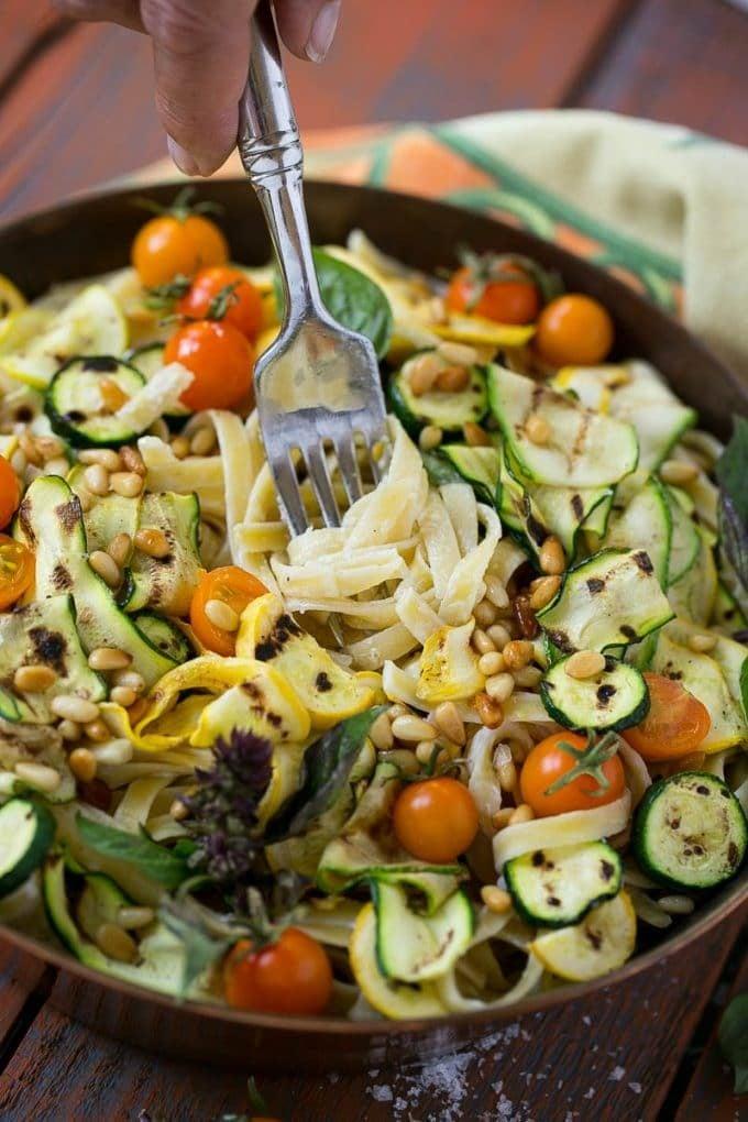 A fork in a bowl of zucchini fettuccine Alfredo pasta.