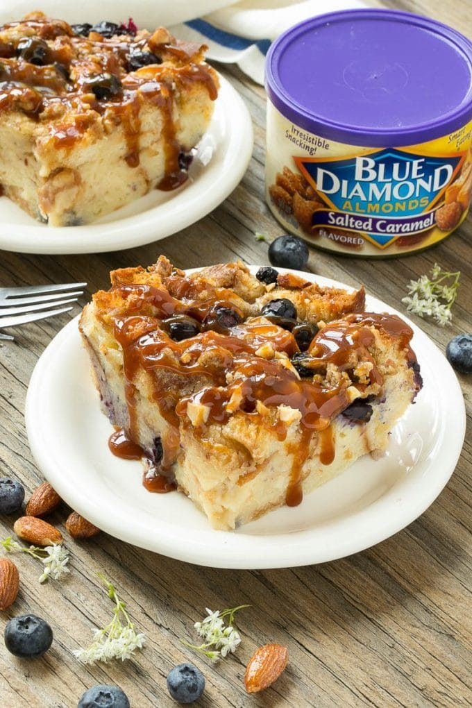 Slices of blueberry bread pudding drizzled with caramel sauce.