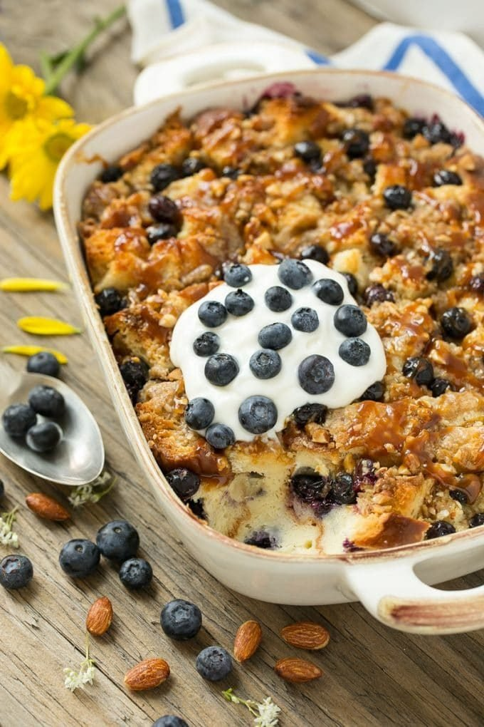 A pan of blueberry bread pudding topped with streusel and caramel sauce.