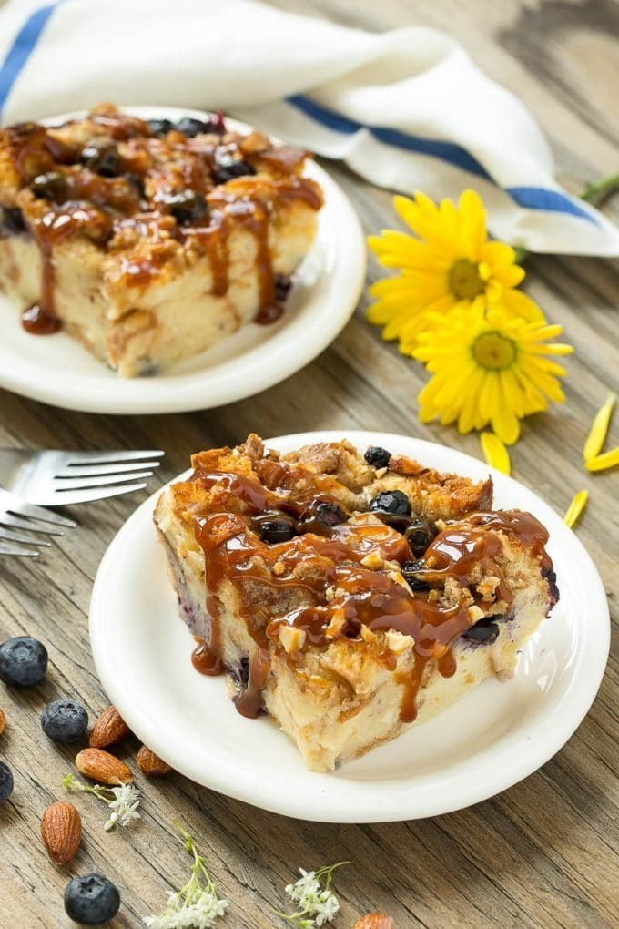 Two pieces of blueberry bread pudding on plates with salted caramel on top.