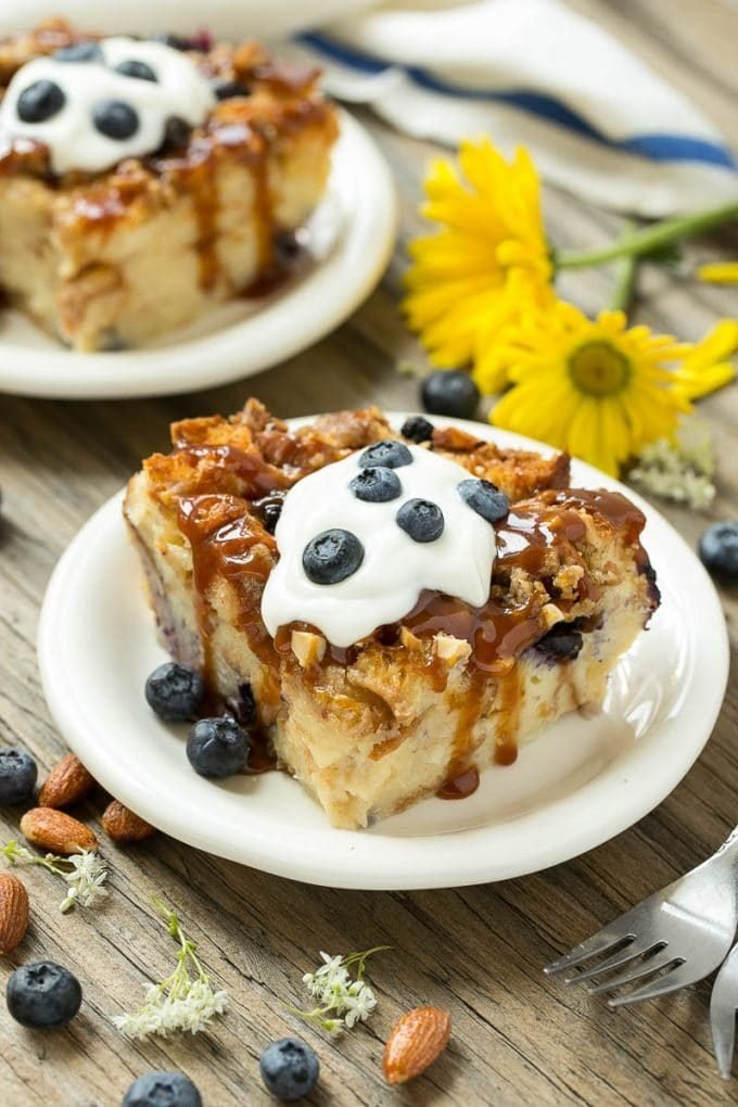 Slices of bread pudding on plates, topped with caramel and fresh berries.