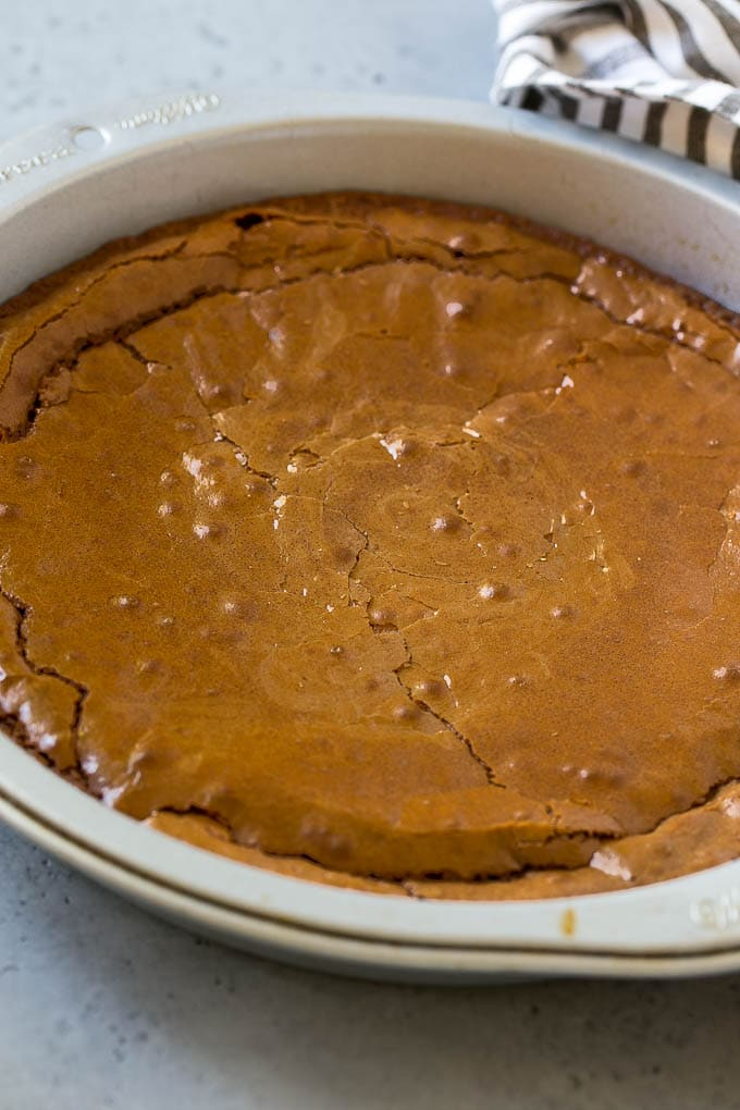 A baked brownie in a round pan.