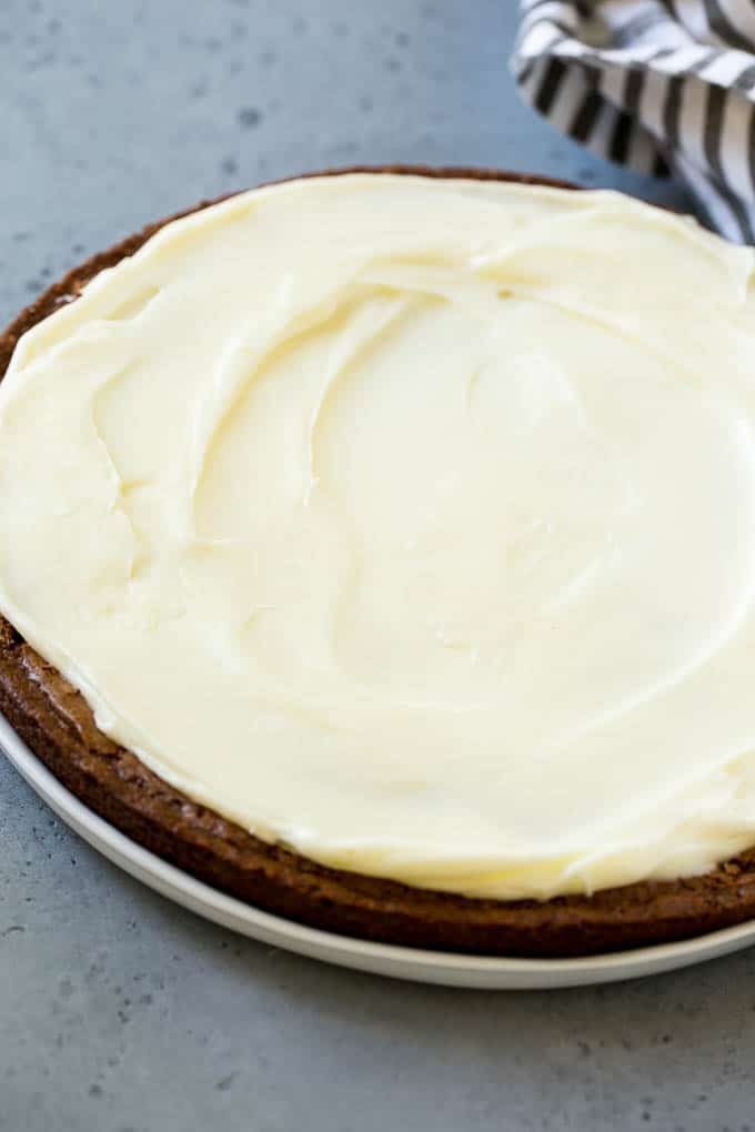 A large round brownie with cream cheese frosting.