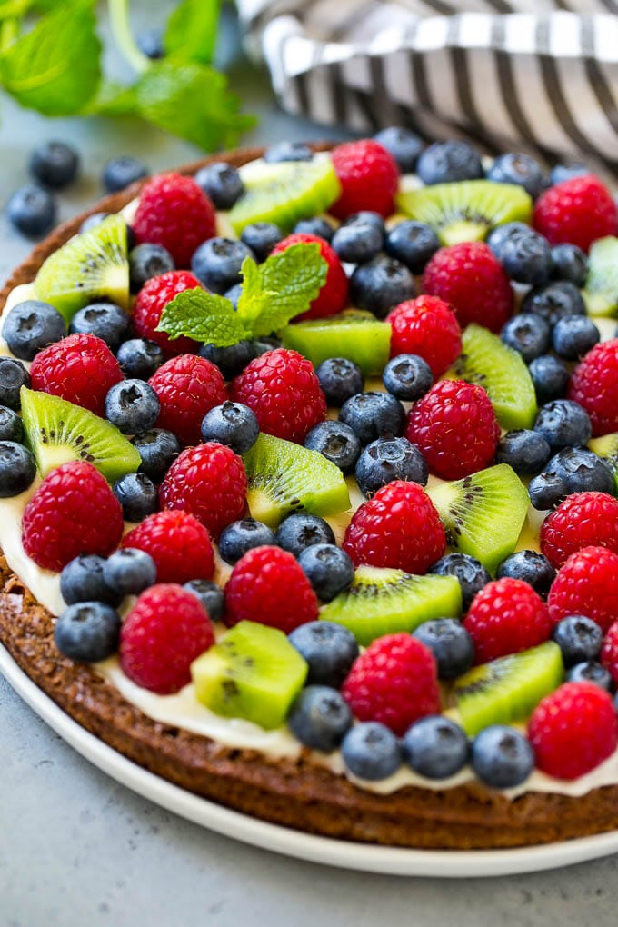 A brownie pizza topped with raspberries, blueberries and kiwis.