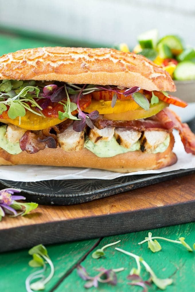 A grilled chicken sandwich with avocado ranch sauce.