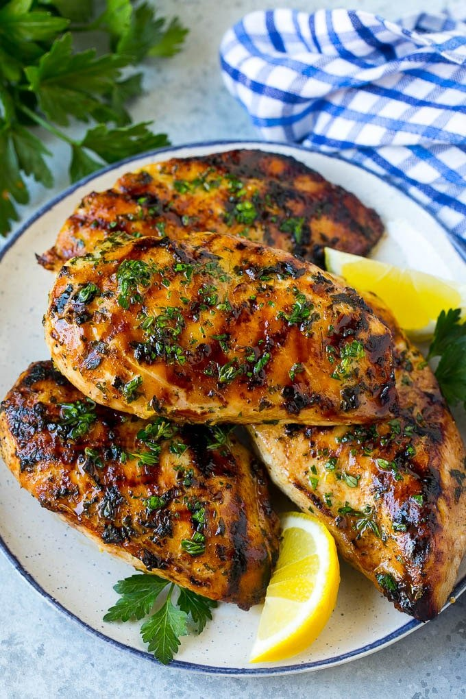 A platter of grilled chicken breast served with parsley and lemon.