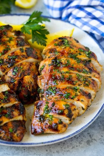 Sliced grilled chicken breast garnished with herbs and lemon.